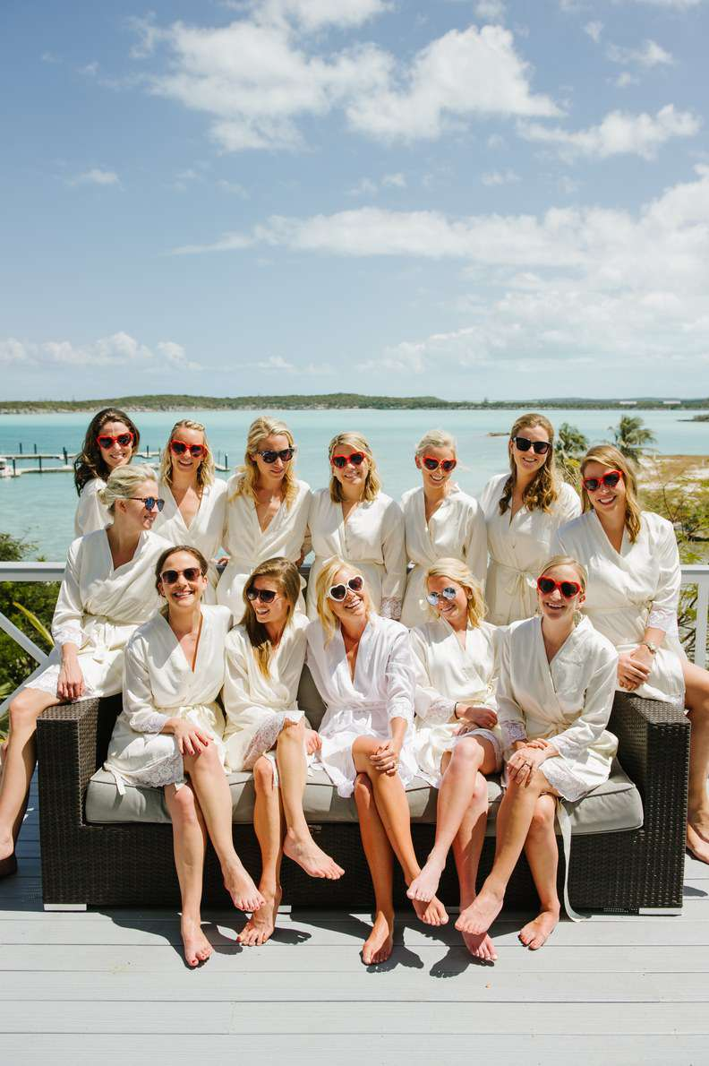 A group of bridesmaids in white robes and matching heart-shaped sunglasses posing outside by the water