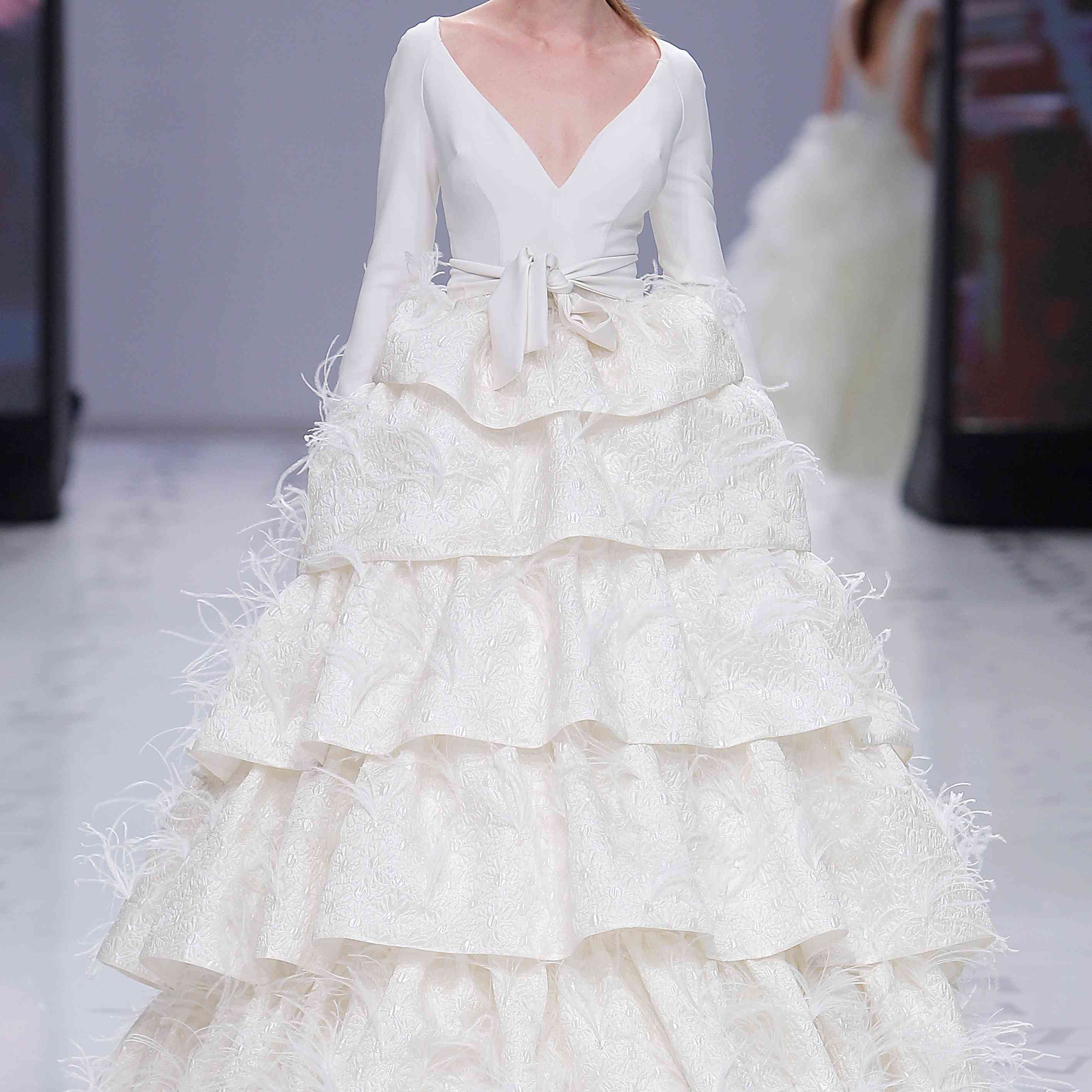 Model in a voluminous princess dress with layers of cloqué ruffles decorated with hand-sewn ostrich feathers and a deep V-neck bodice with raglan sleeves finished with a knotted belt at the waist