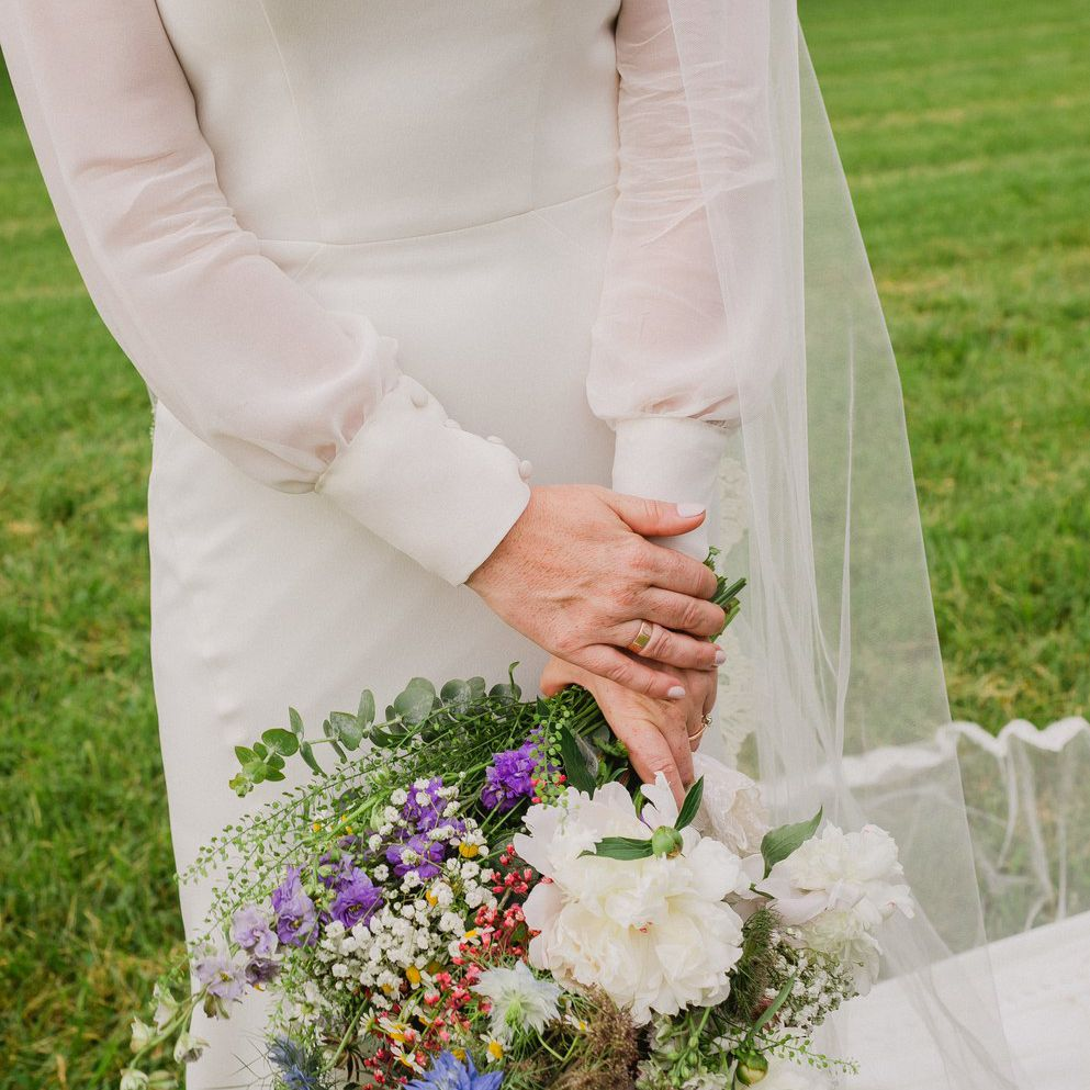 Bride holding a small multicolored bouquet of wildflowers