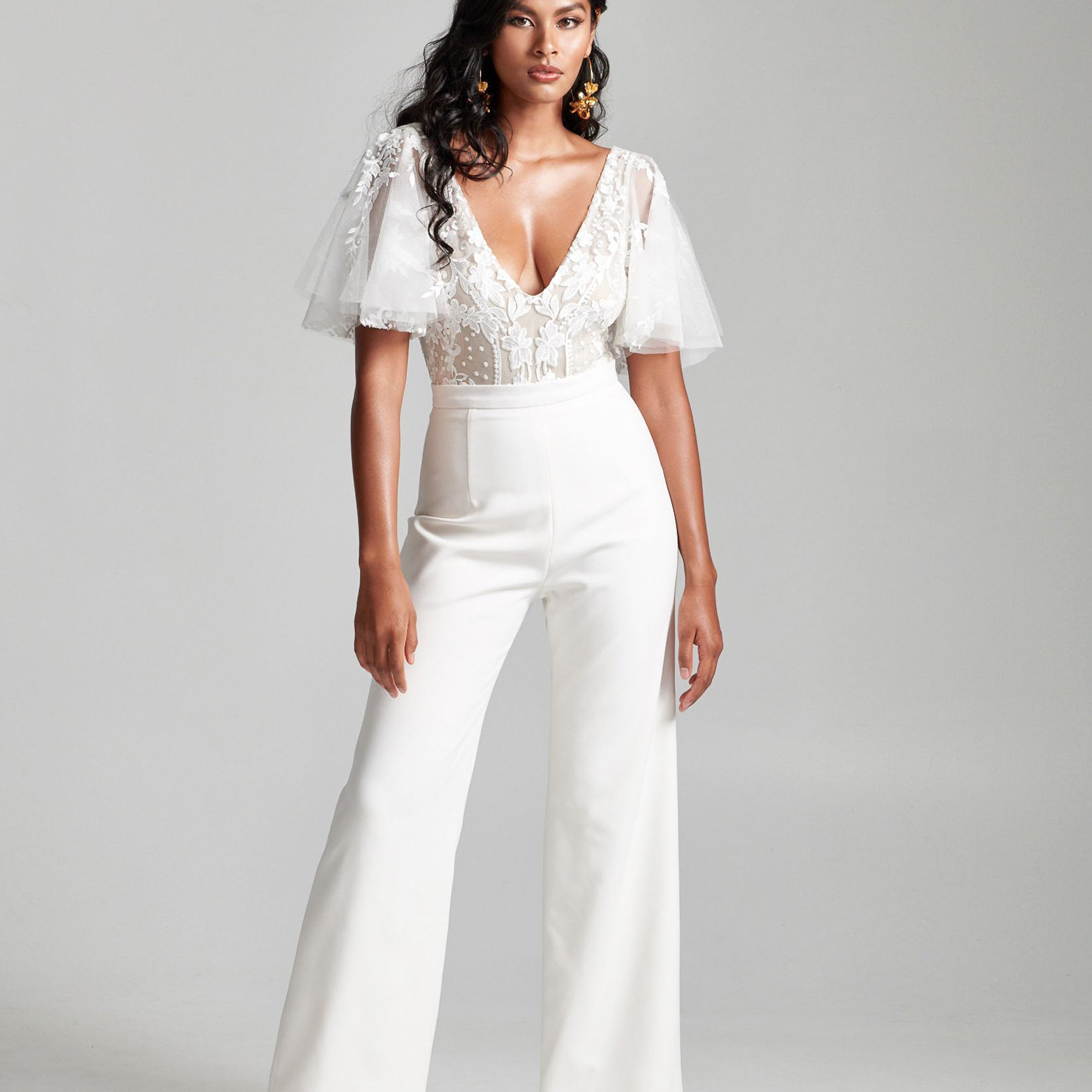 Model in lace v-neck top with flutter sleeves and wide leg high-waisted pants