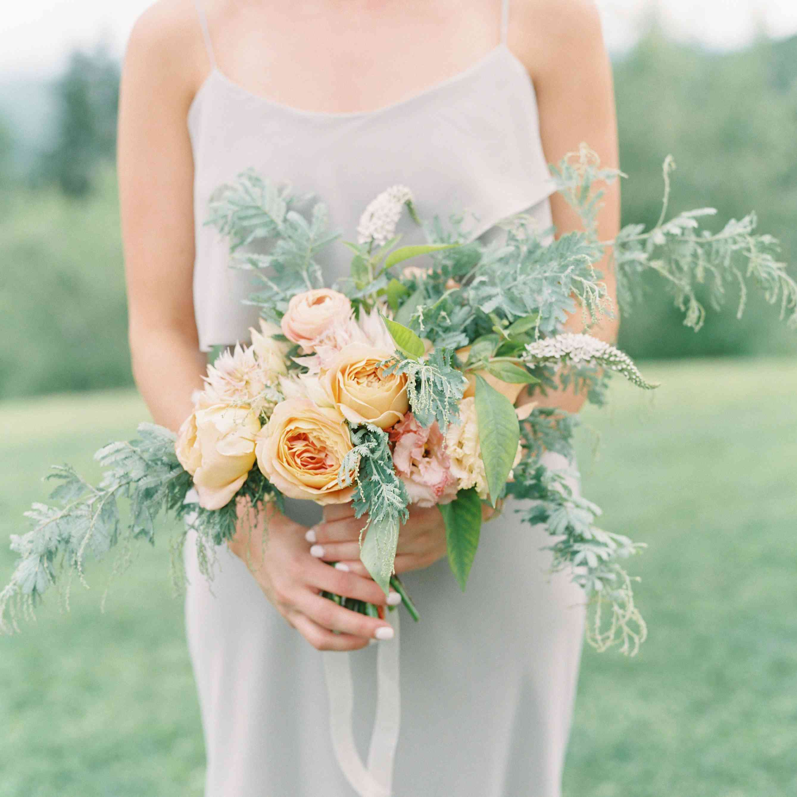 Bridesmaid carrying bouquet of peach and pink roses