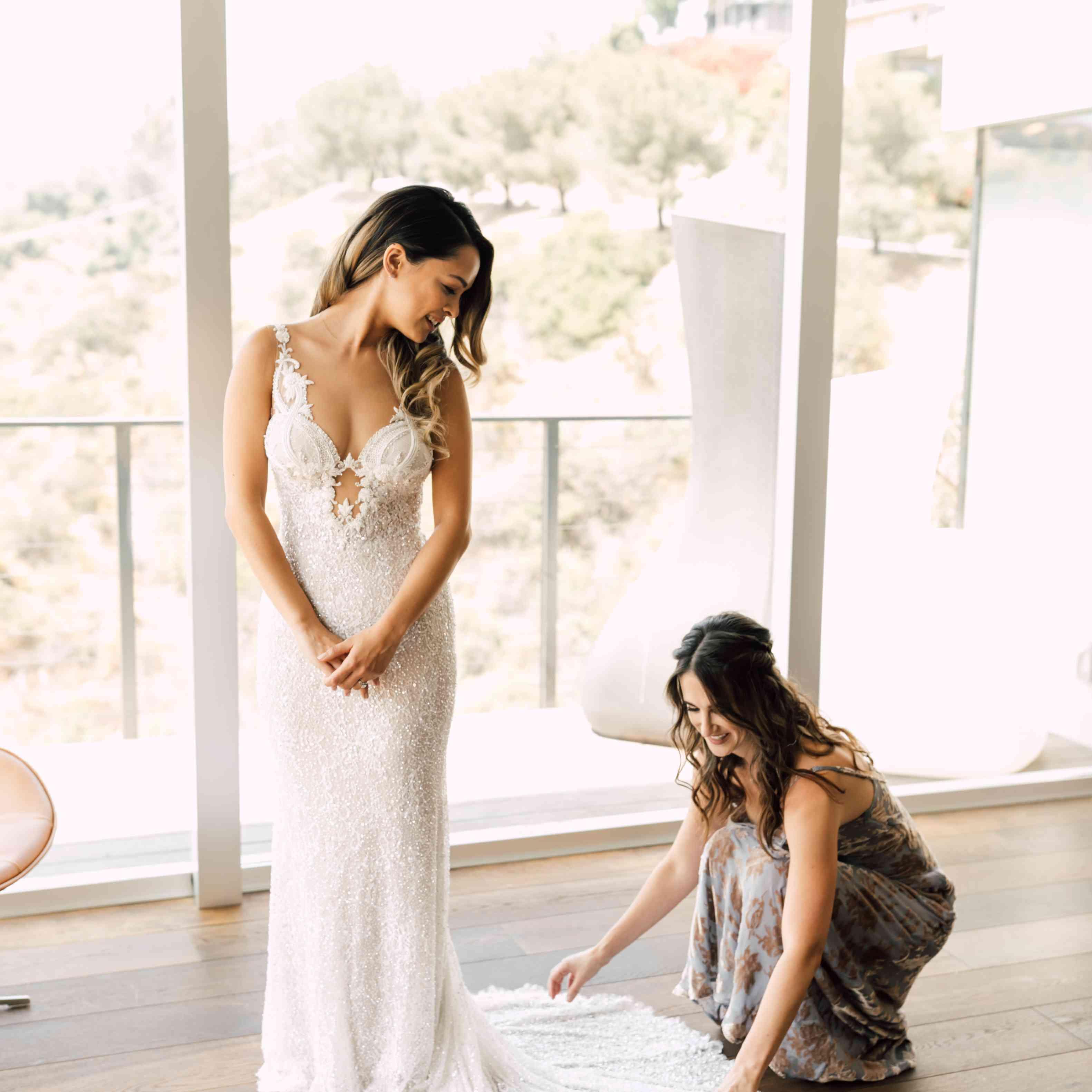 bride's friend fixing dress
