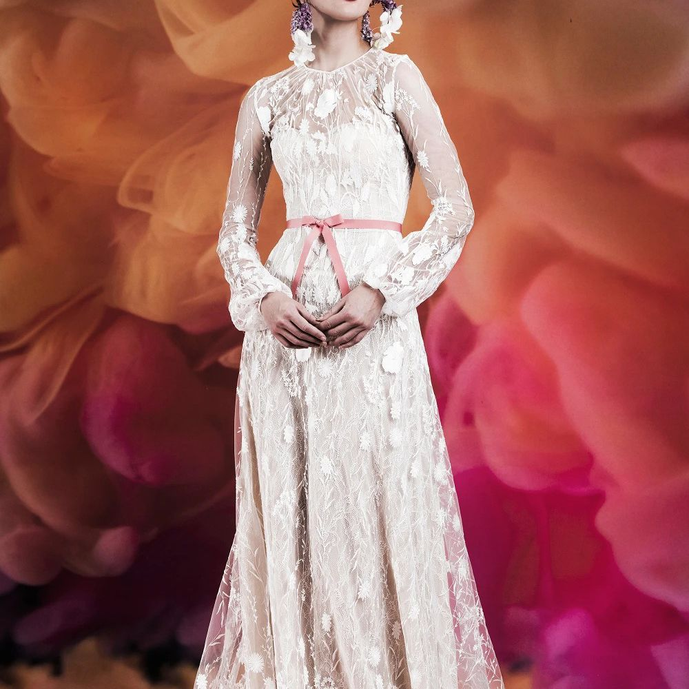 Model in long-sleeve embroidered gown with puff sleeves