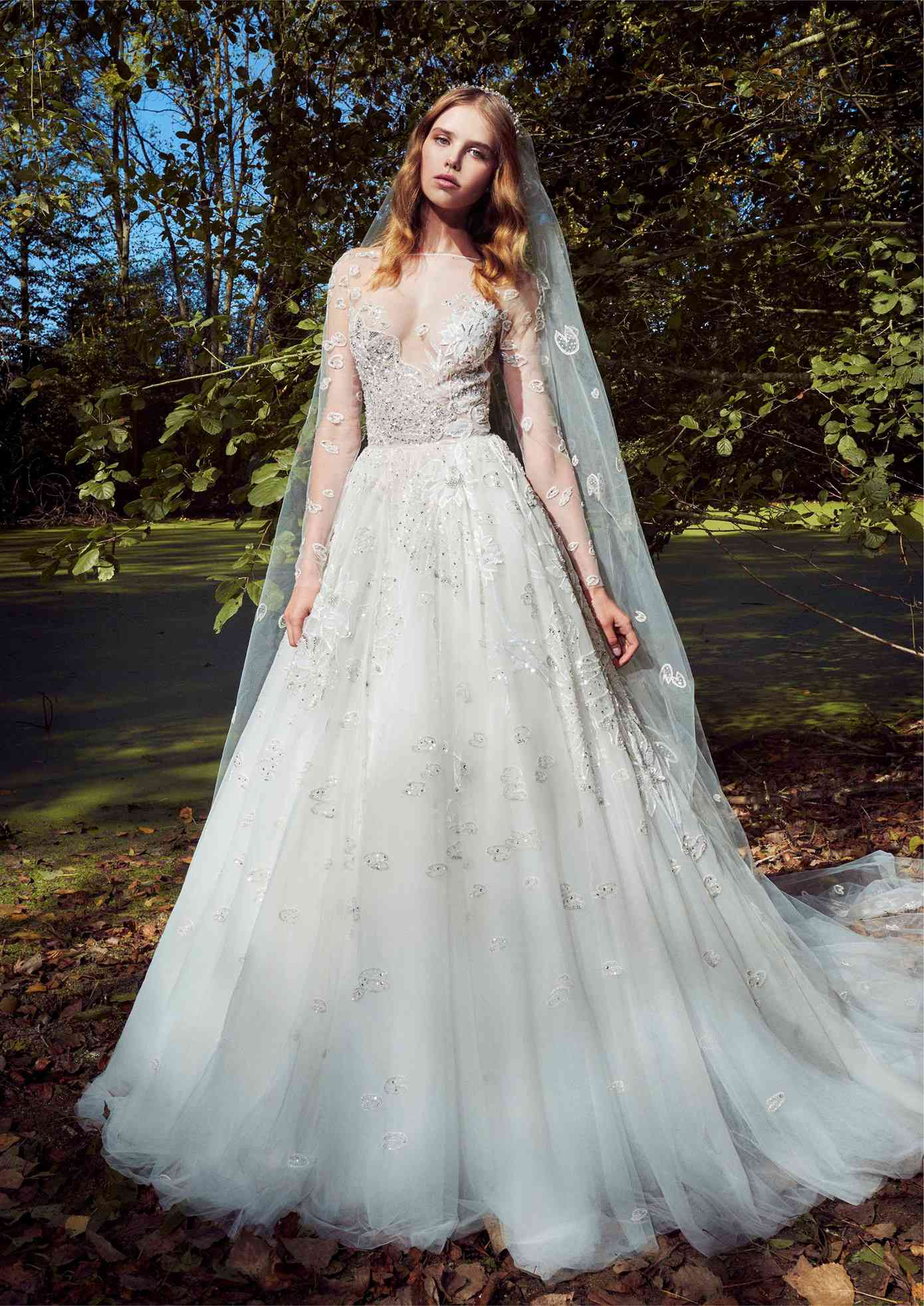 Model in tulle ballgown with illusion long sleeves and neckline with silver sequined embroidery and a matching veil