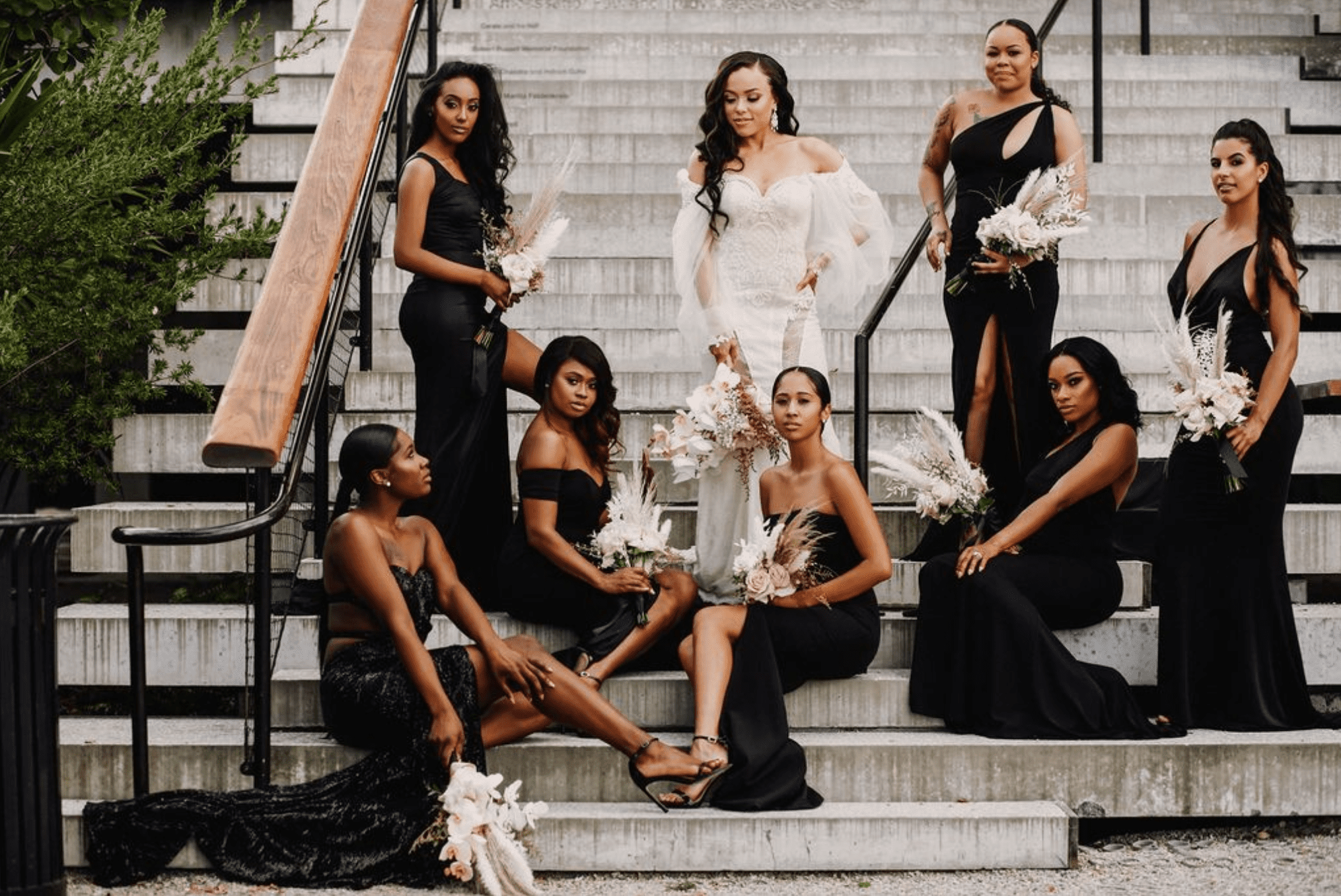 Bride with fashionable bridesmaids in black gowns