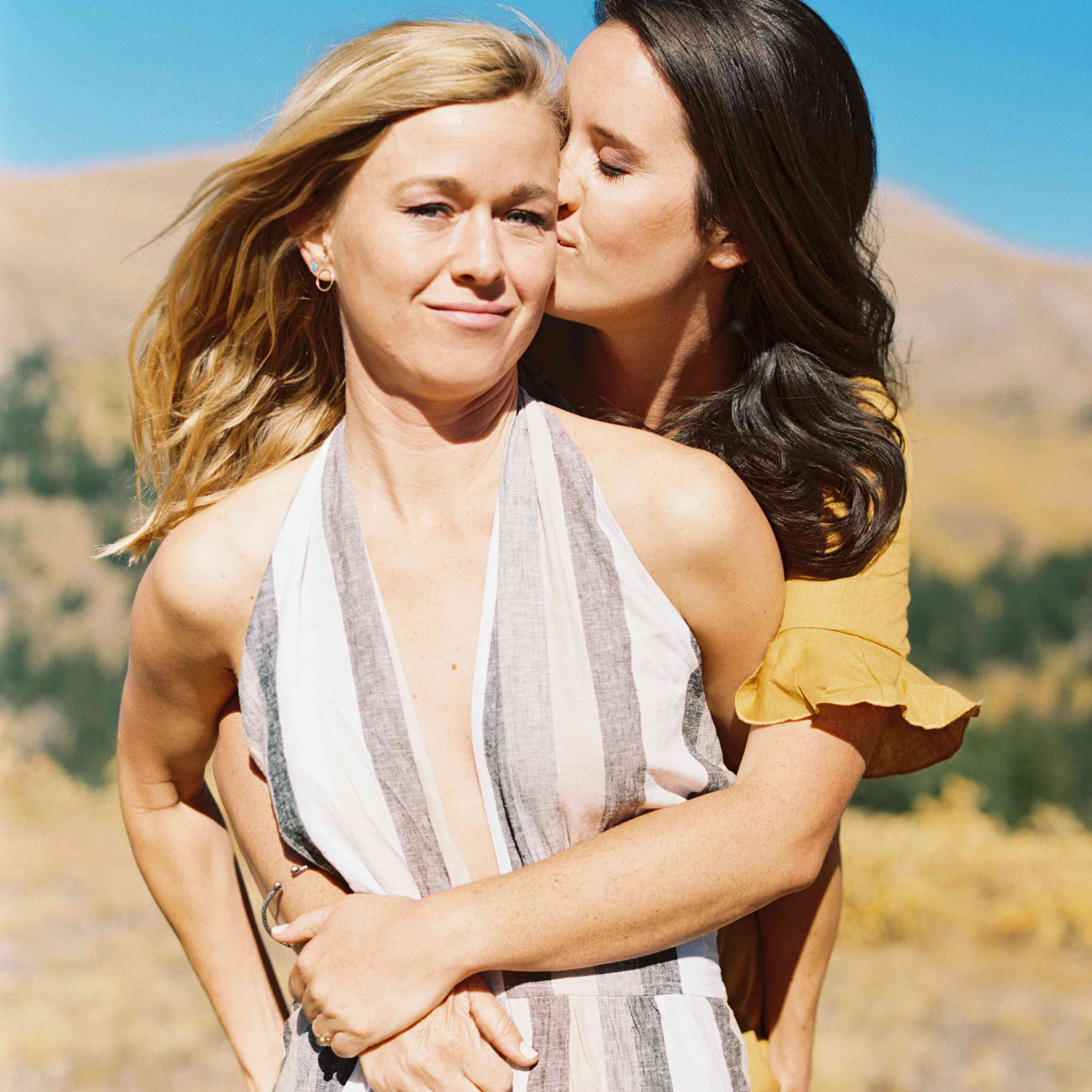 Bride-to-be hugging fiancee and kissing her temple in a desert landscape