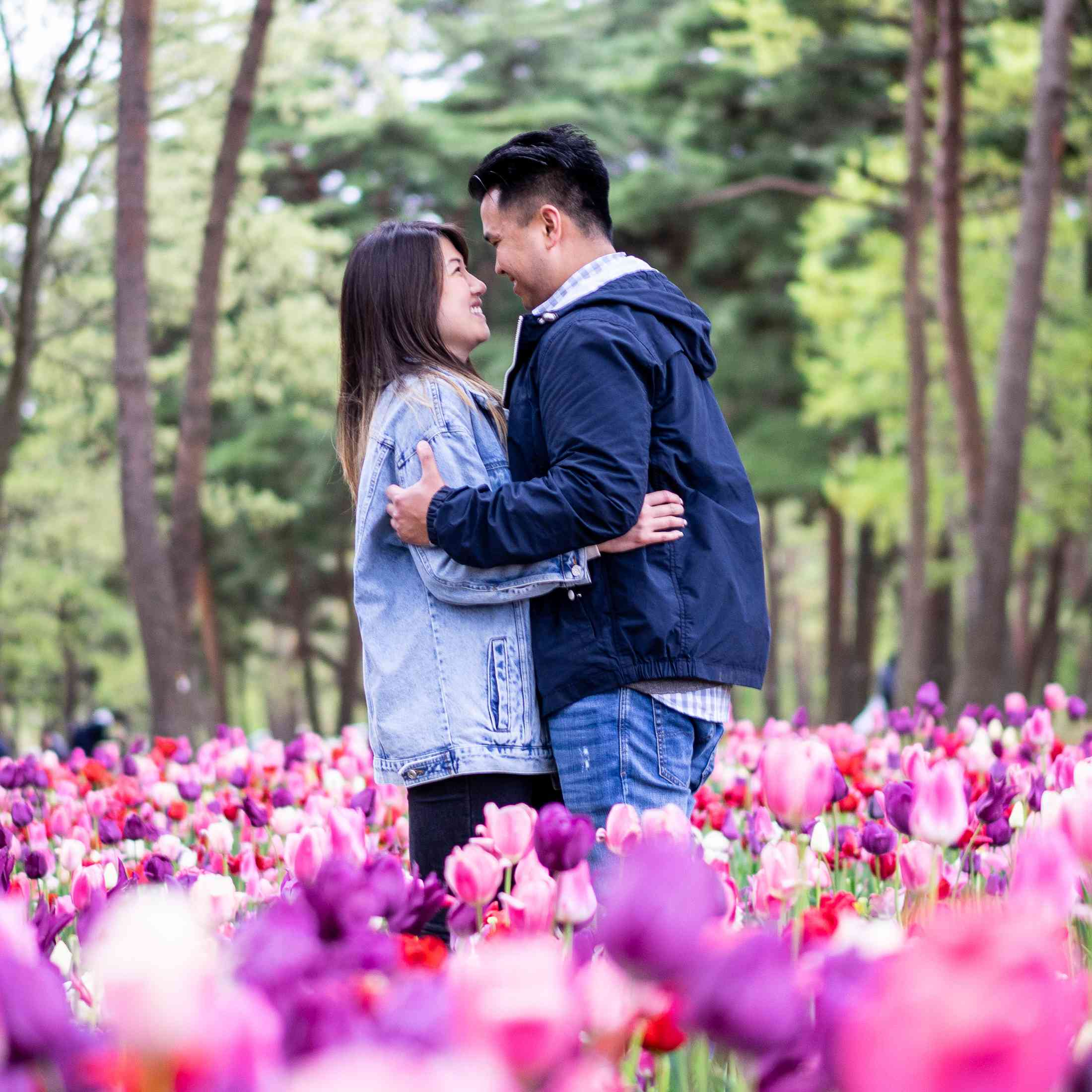 Couple embracing while standing in tulip field