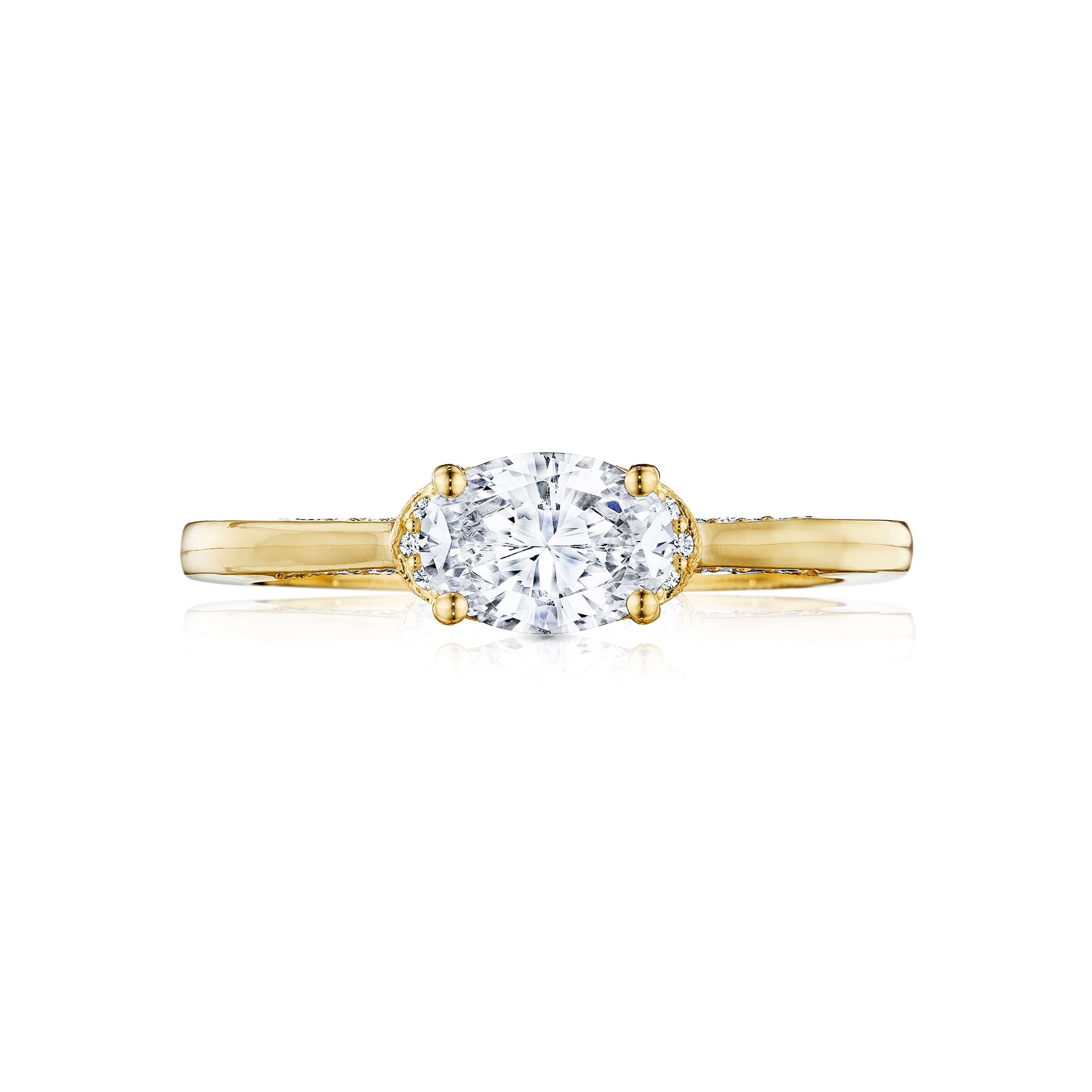 East-west oval diamond engagement ring with yellow gold band on a white background.