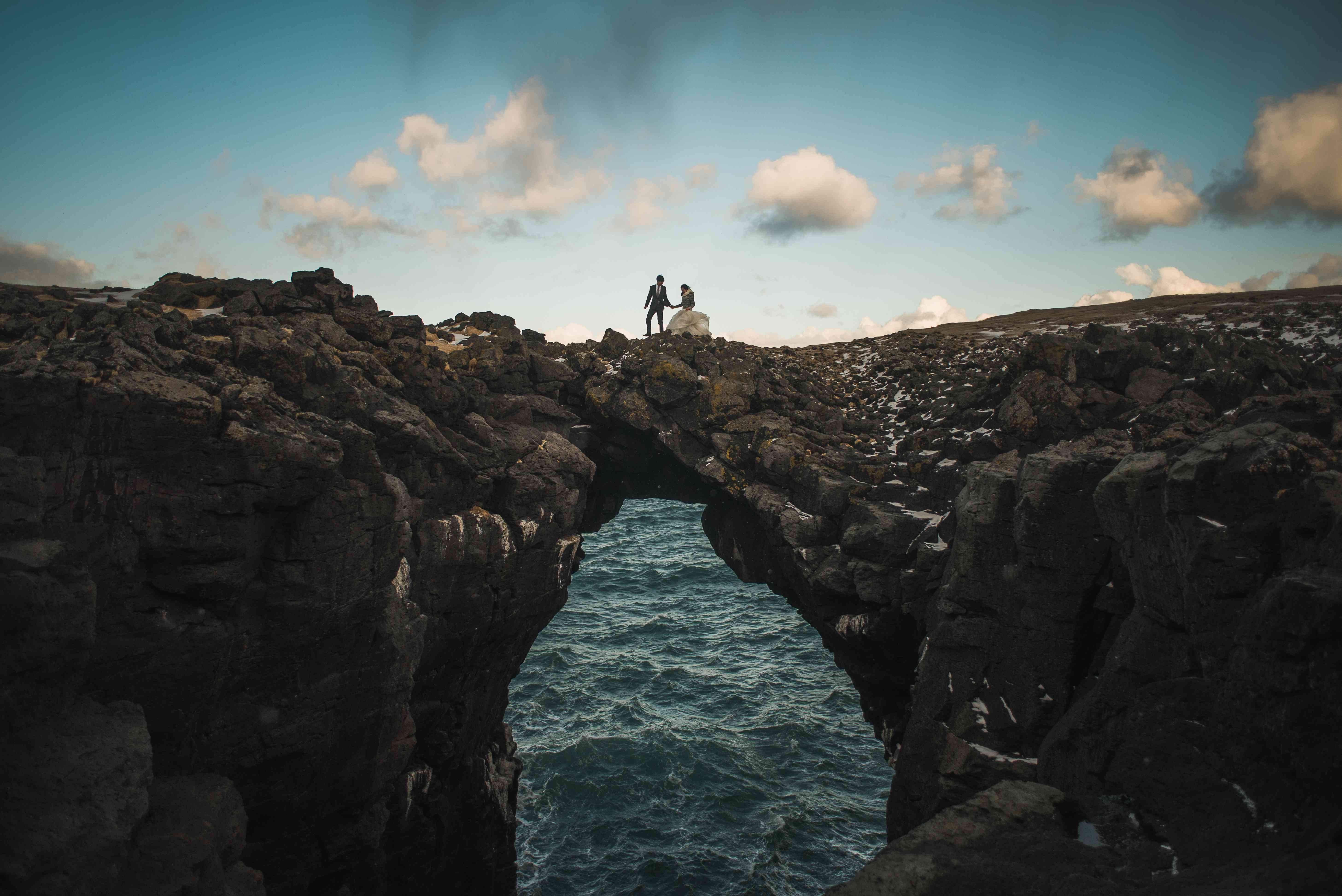 Couple on top of Gatklettur Arch Rock in Iceland