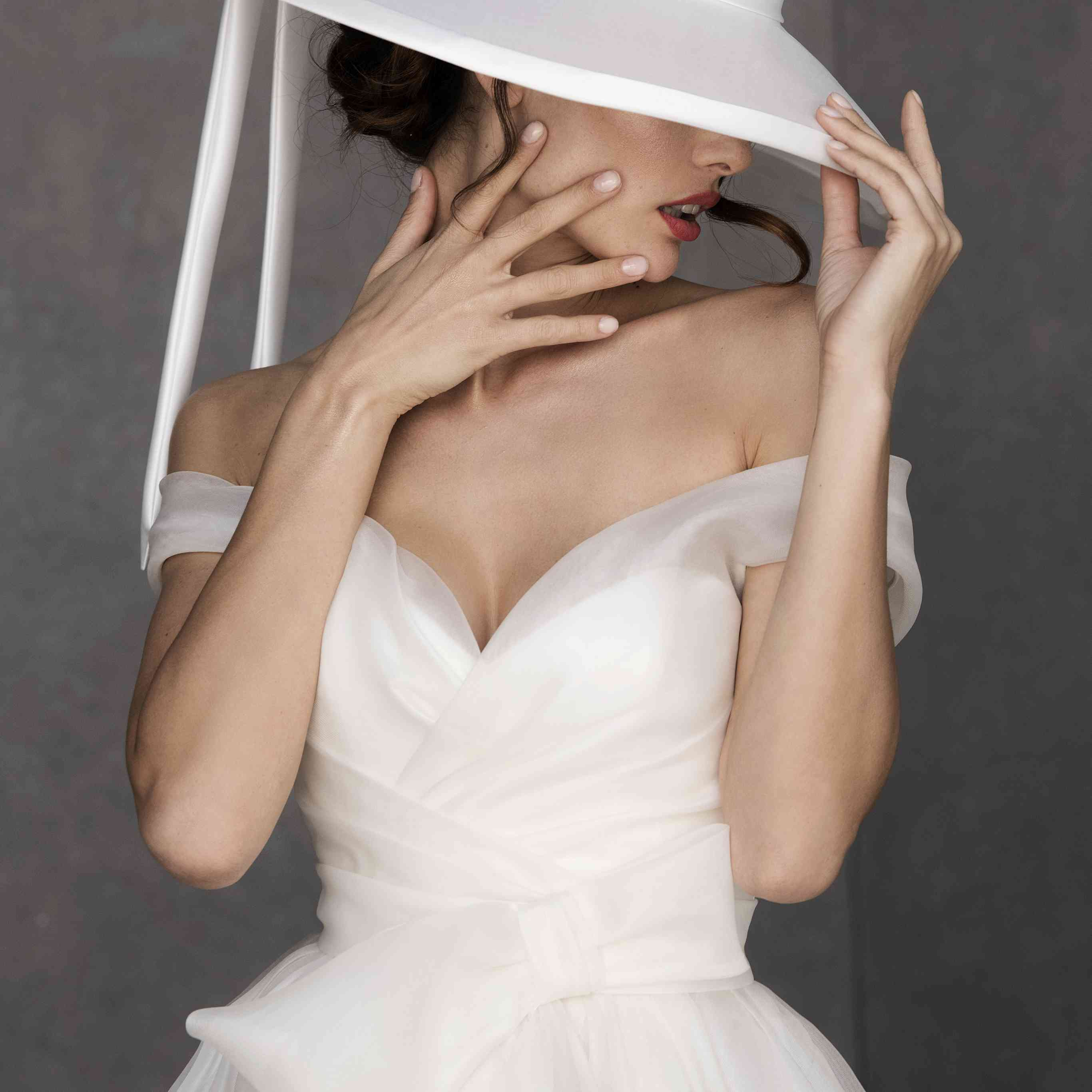 Model in an off-the-shoulder wrap-effect tulle ballgown with big bow detail wearing a wide-brimmed white hat