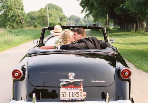 Bride and groom kissing in back of black convertible