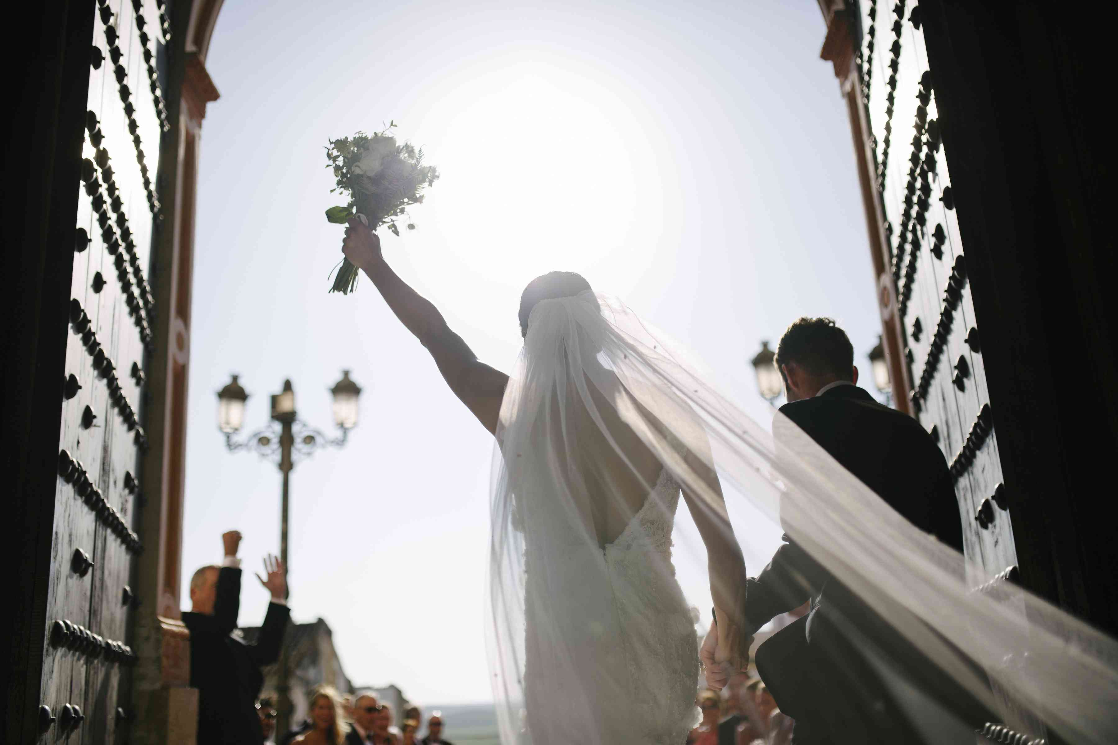 Bride holding up bouquet as she and the groom exit their ceremony