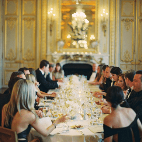 Wedding guests seated at a long table in a regal white and gold indoor venue