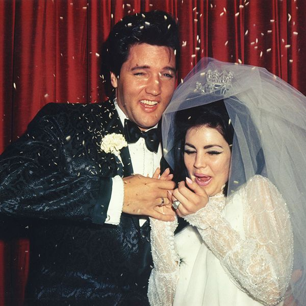 Elvis and Priscilla Presley laughing as confetti is thrown into their faces on their wedding day