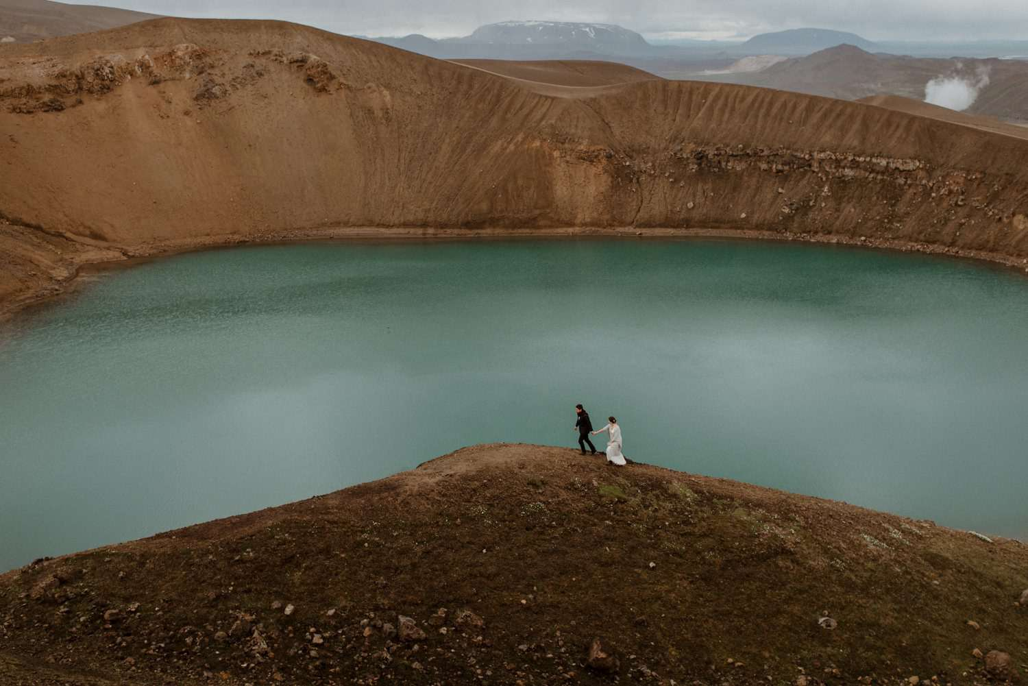 Couple holding hands at Viti Crater in Iceland