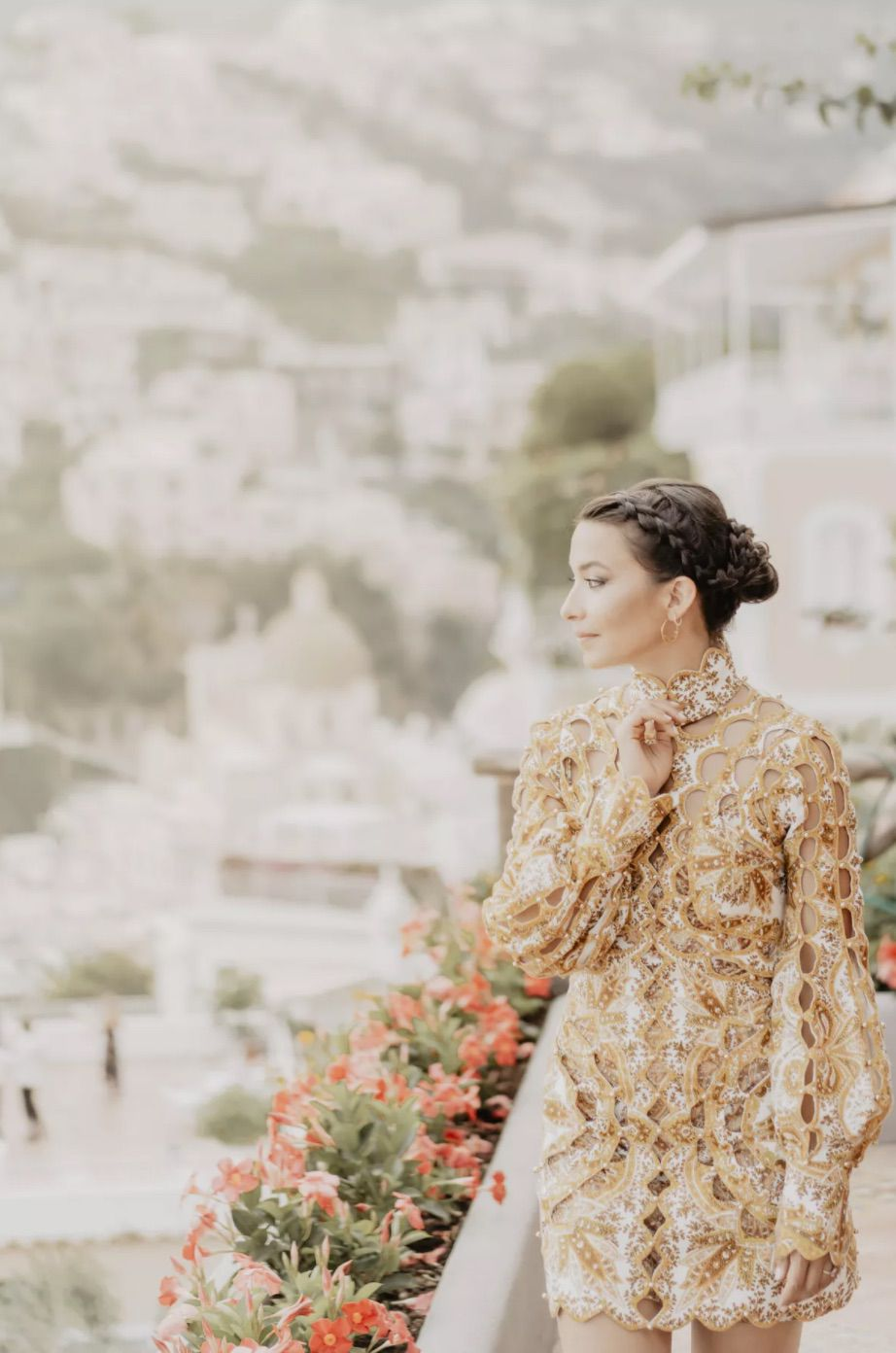 Bride in braided updo looking out of floral lined balcony