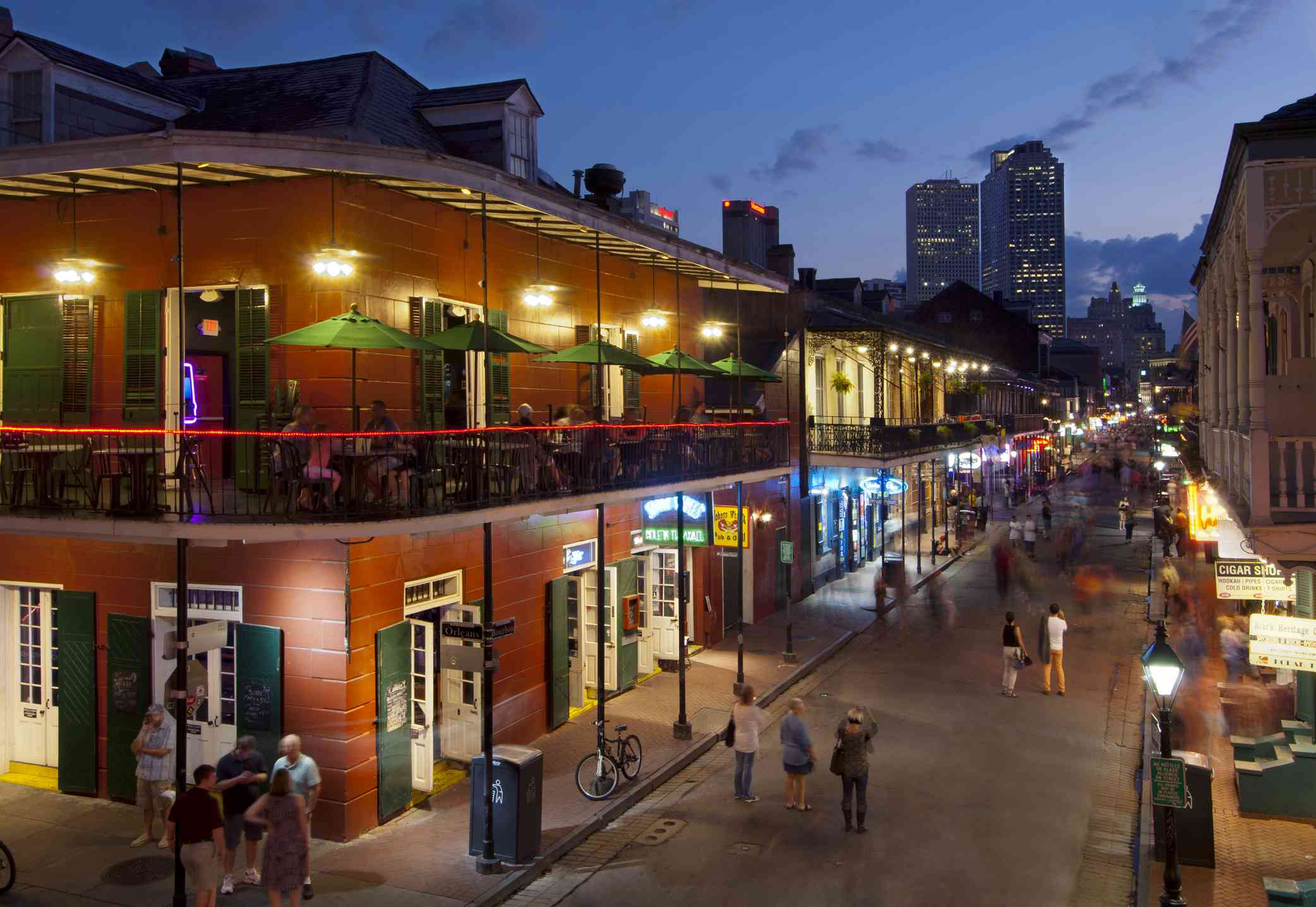 People walking and dining on Bourbon Street at night in New Orleans
