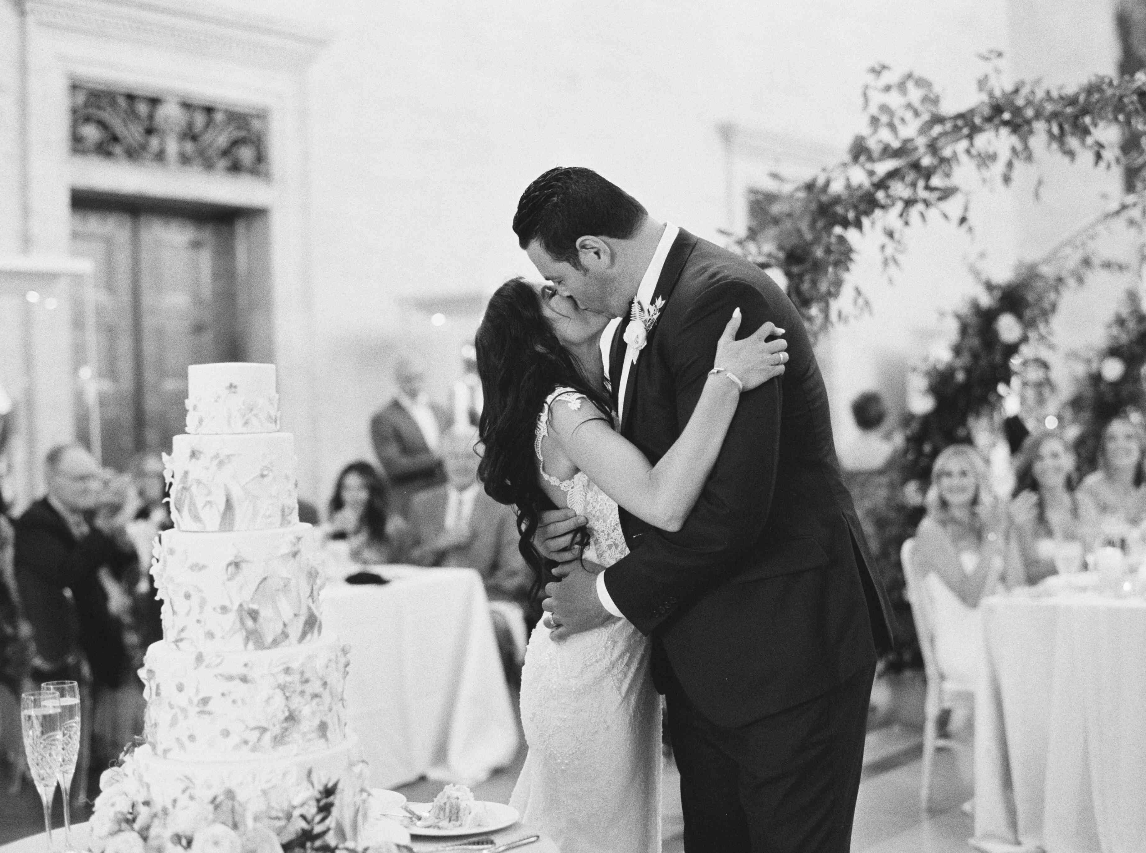 The couple kisses after cutting their wedding cake