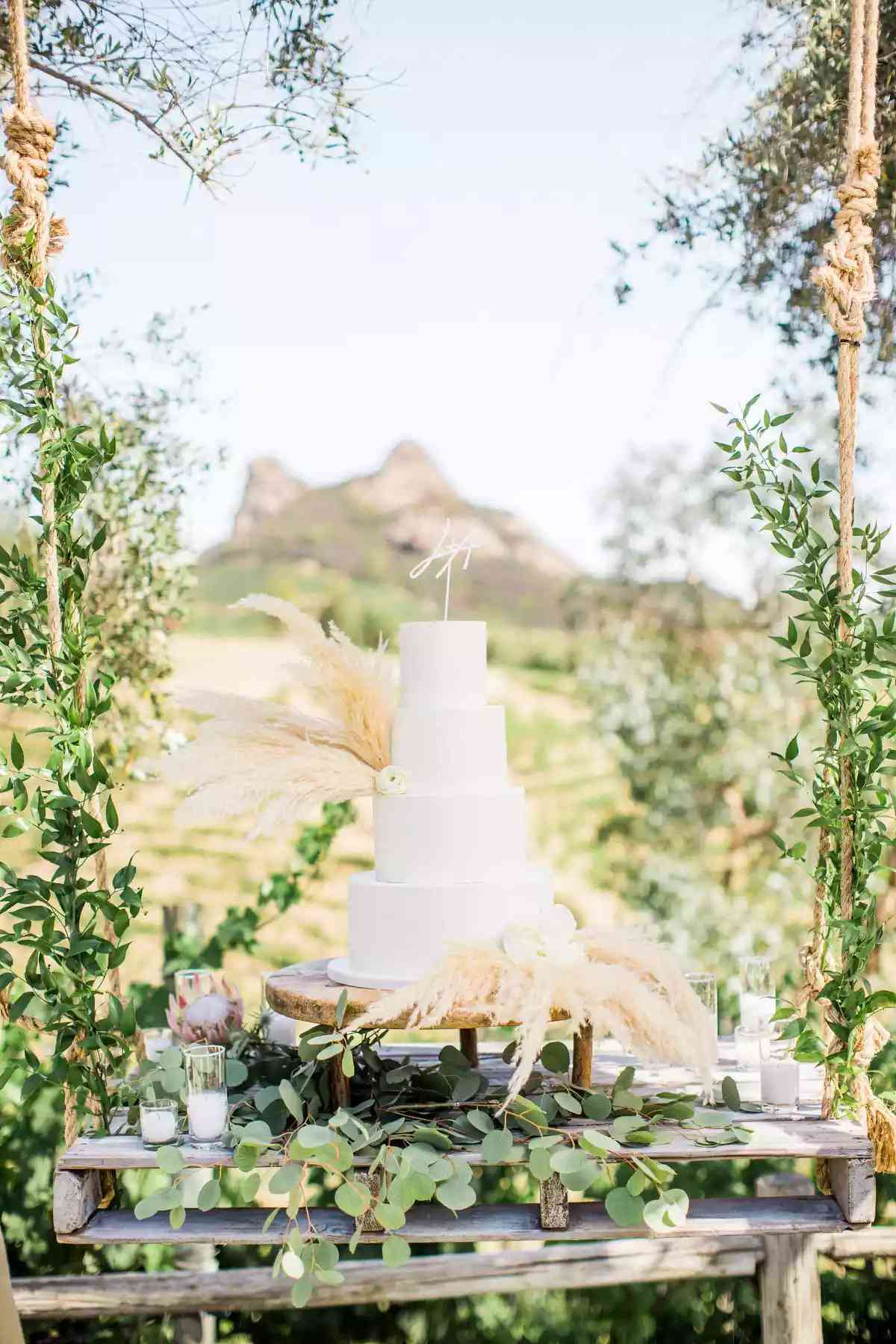 White wedding cake surrounded by greenery