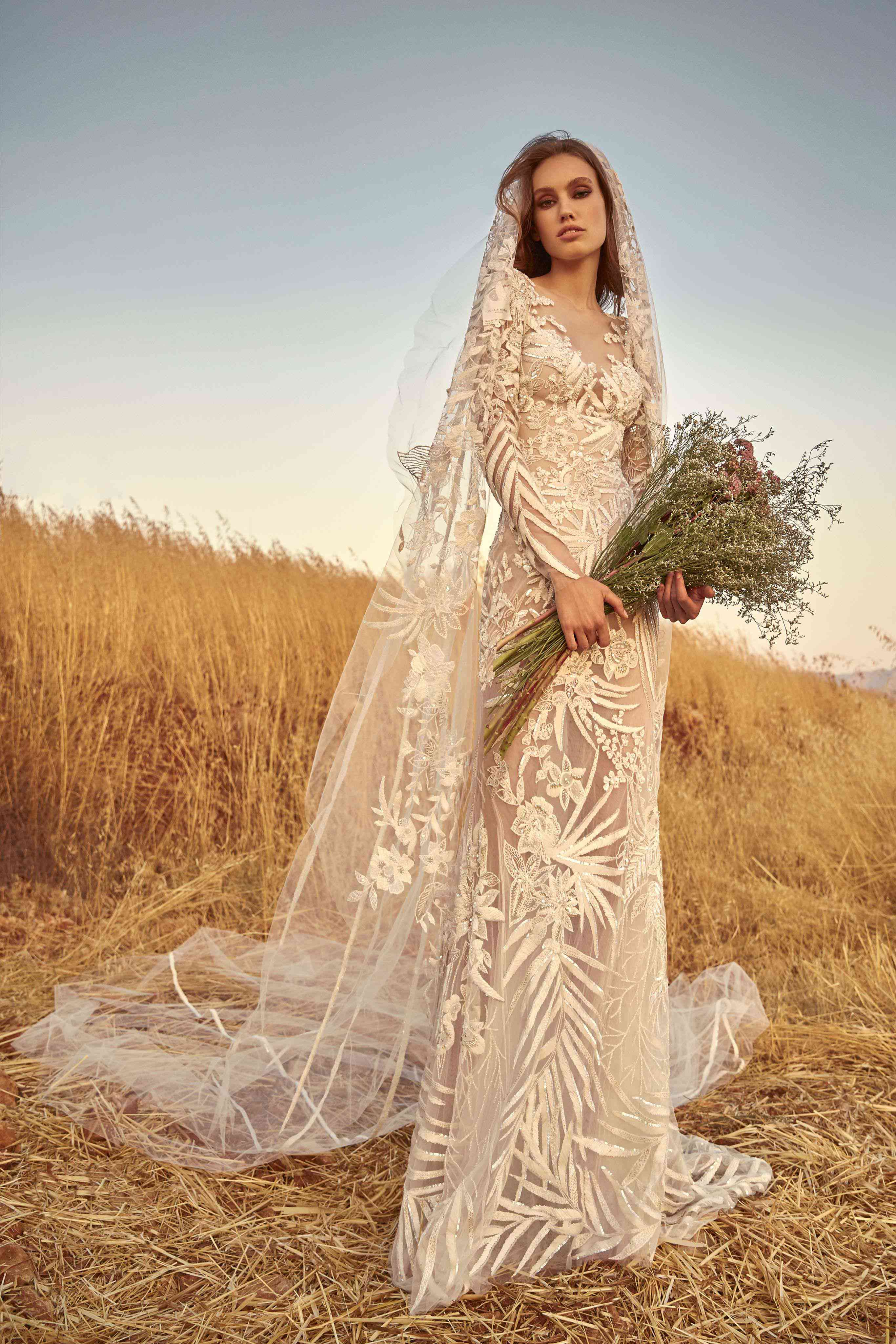 Model in a fitted fully embroidered off-white long-sleeve dress with a matching veil