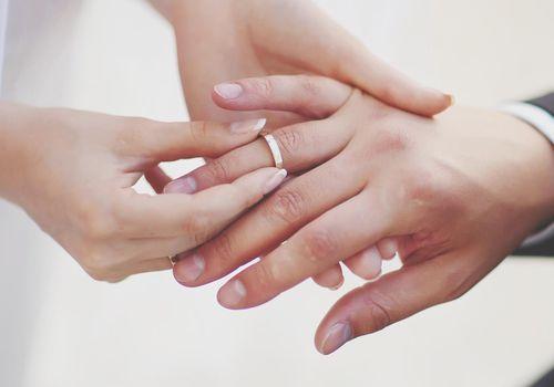 bride putting ring on groom