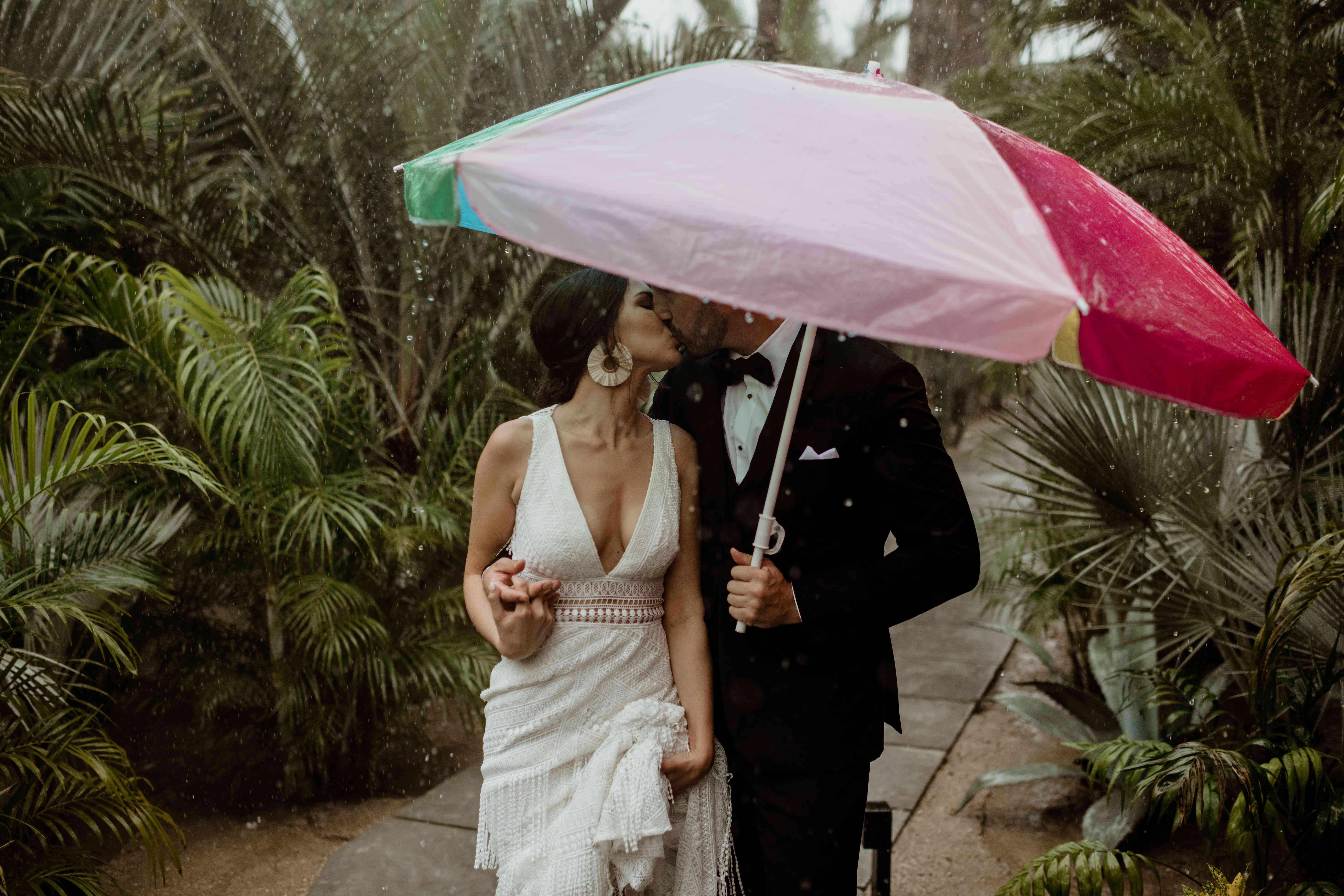 Newlyweds kissing under beach umbrella in the rain