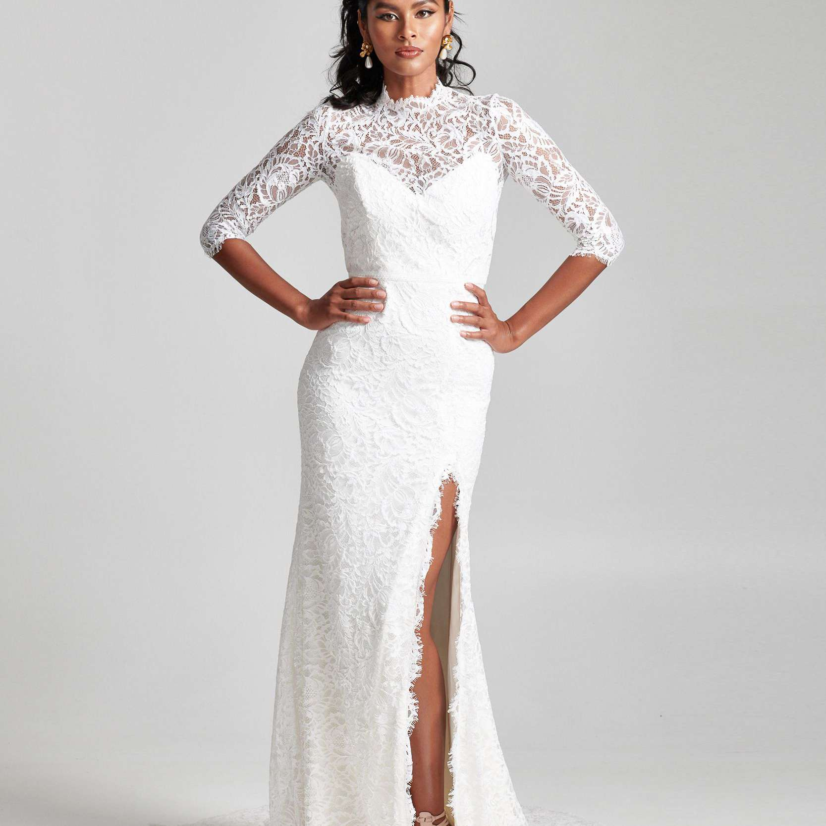 Model in floral lace dress with skirt slit and high neck lace long sleeve topper