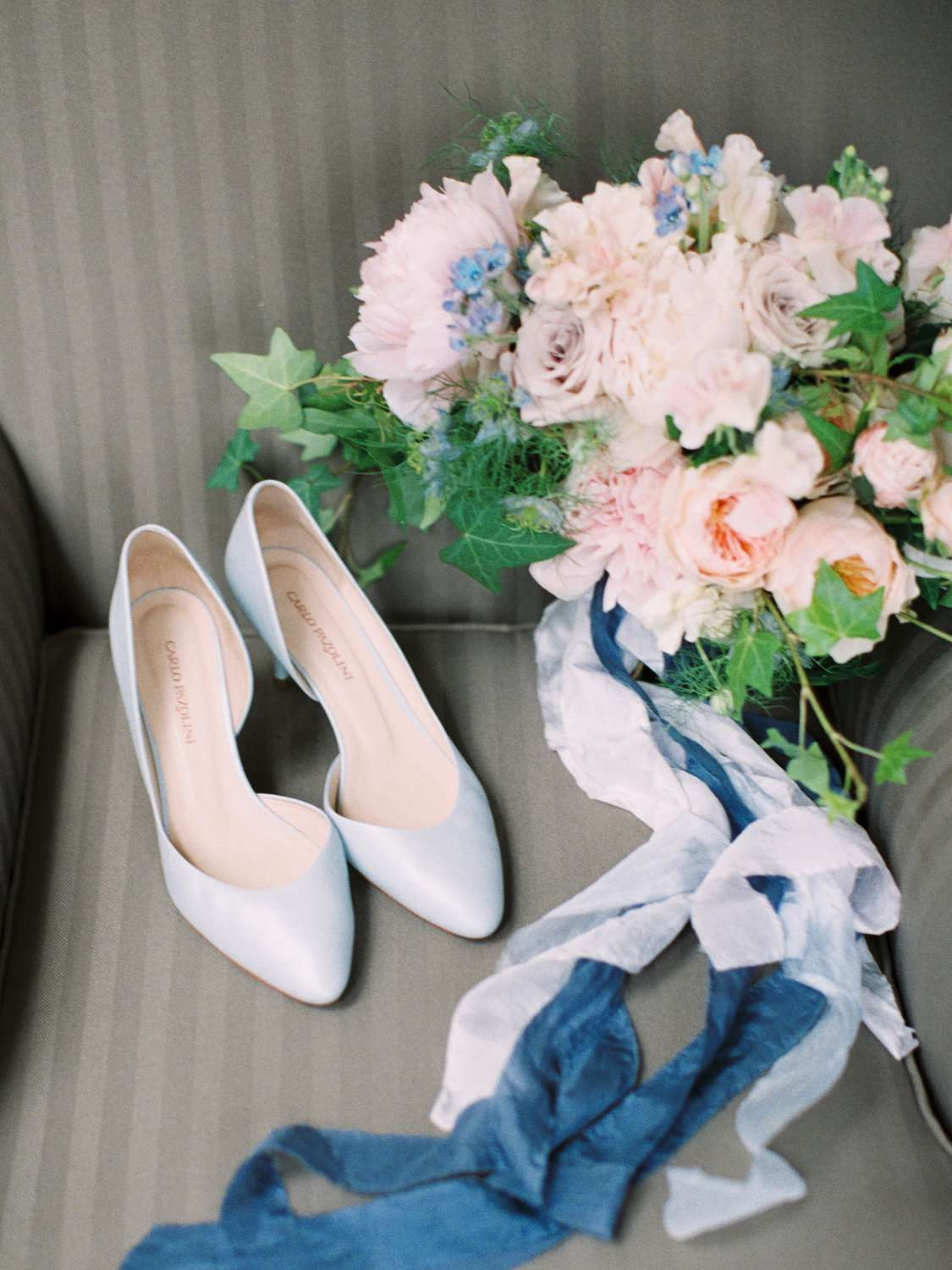 A pair of blue wedding shoes on a chair.